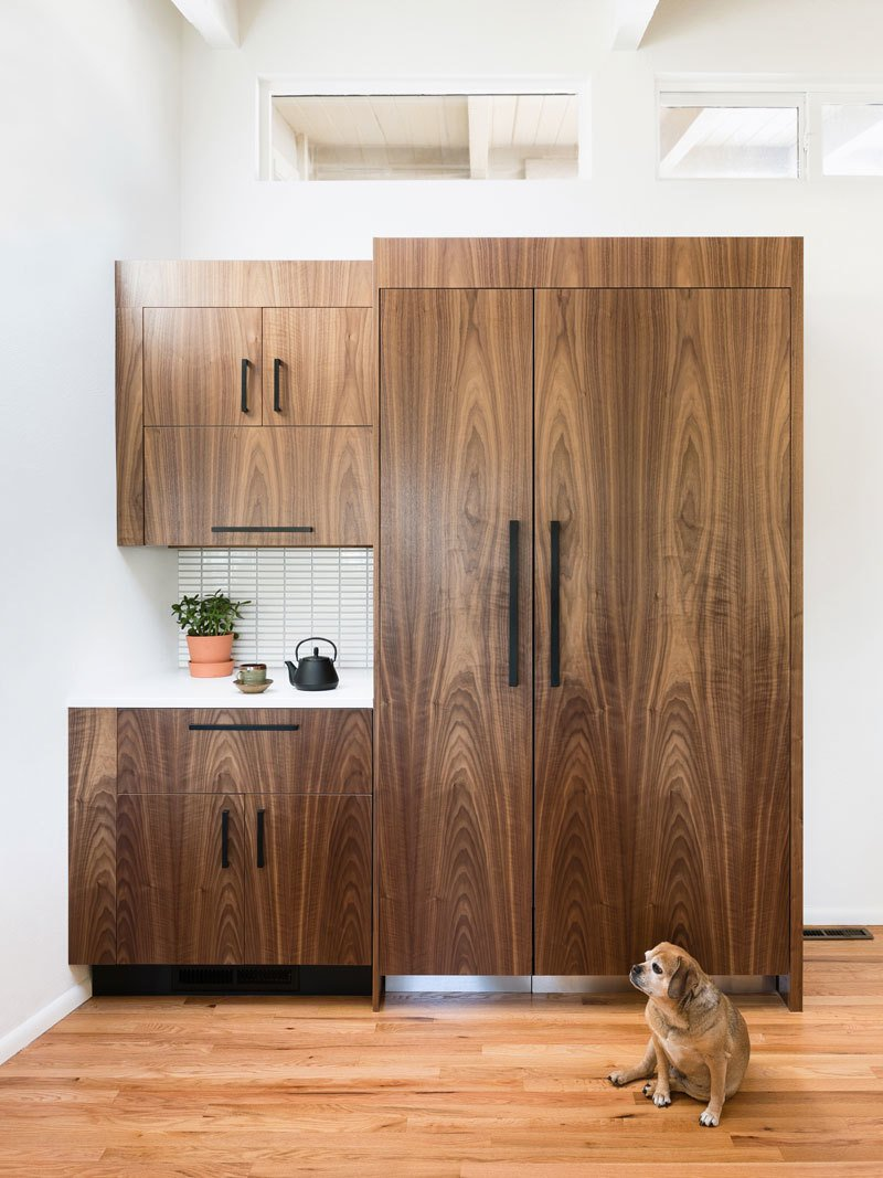 The fridge is concealed behind grain-matched walnut doors (and a very cute dog).