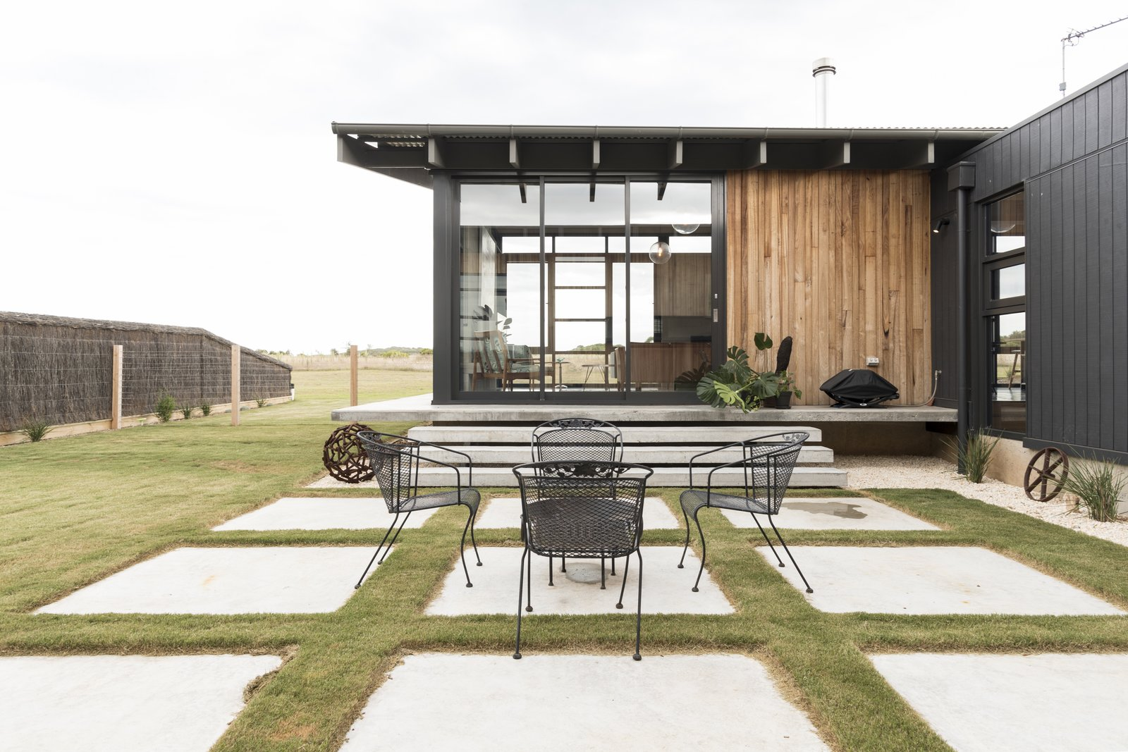 Outdoor, Grass, Concrete Patio, Porch, Deck, Side Yard, Wire Fences, Wall, Large Patio, Porch, Deck, Horizontal Fences, Wall, and Pavers Patio, Porch, Deck Courtyard   The Golf Course House by Bespoke Architects