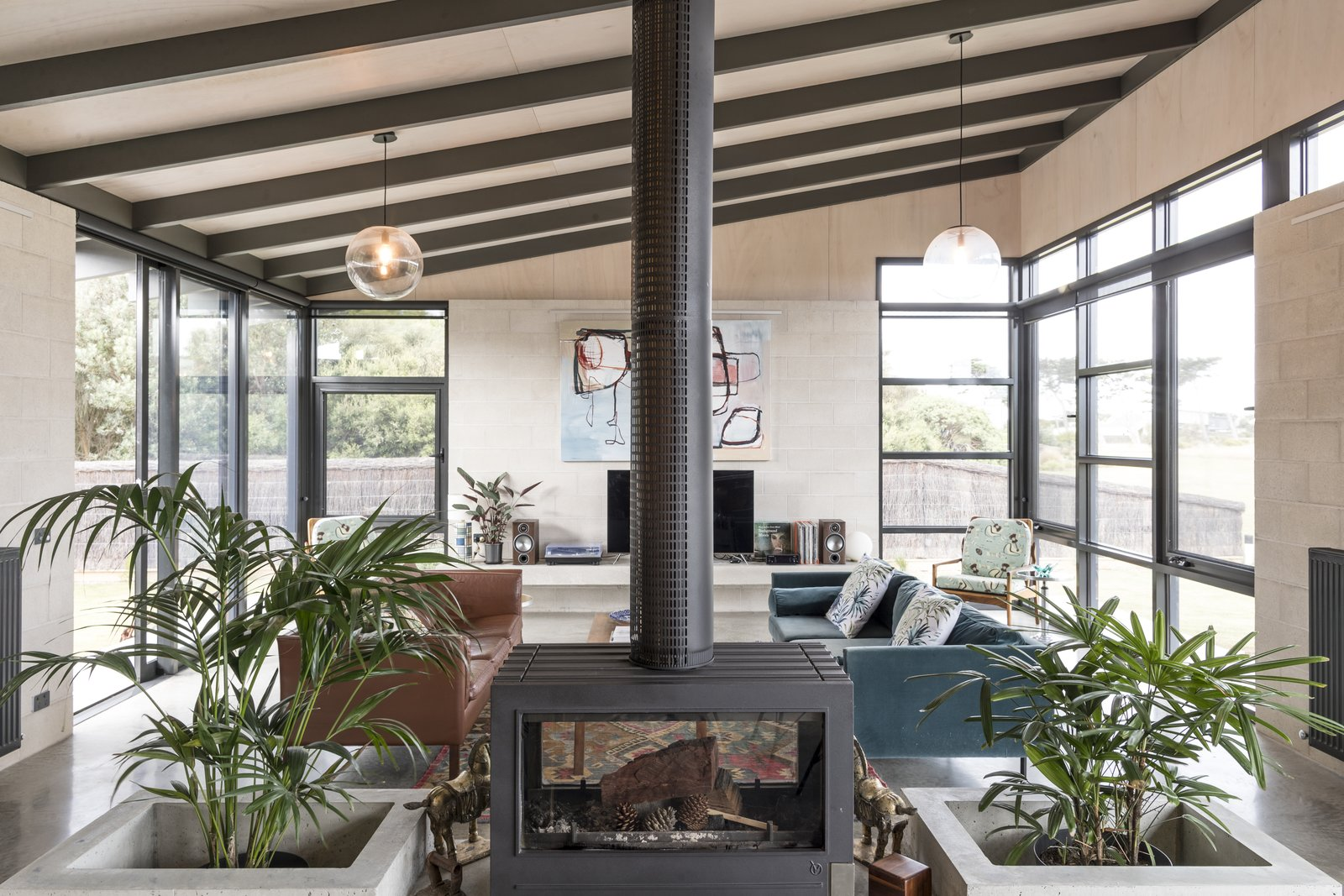 Living Room, Ceiling Lighting, Chair, Concrete Floor, Two-Sided Fireplace, Wood Burning Fireplace, Pendant Lighting, Sofa, and Coffee Tables Living   The Golf Course House by Bespoke Architects