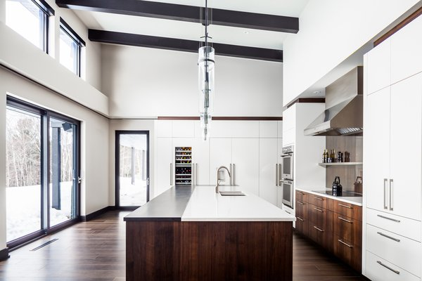 The kitchen in this cabin is unique among white kitchens with black countertops due to a half-black, half-white countertop design. Here, the white part is stone, while the black part is an espresso-stained wood, which mirrors the exposed beams above.