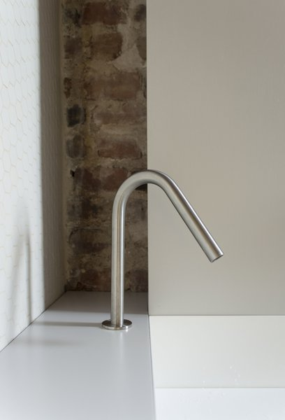 The bathroom sink is large, yet thin metal walls keep it unobtrusive.