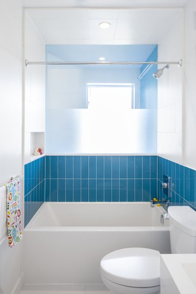 Bathroom with borrowed light and view across a double height volume