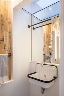 Powder room with borrowed light from glass ceiling over hung wall sink