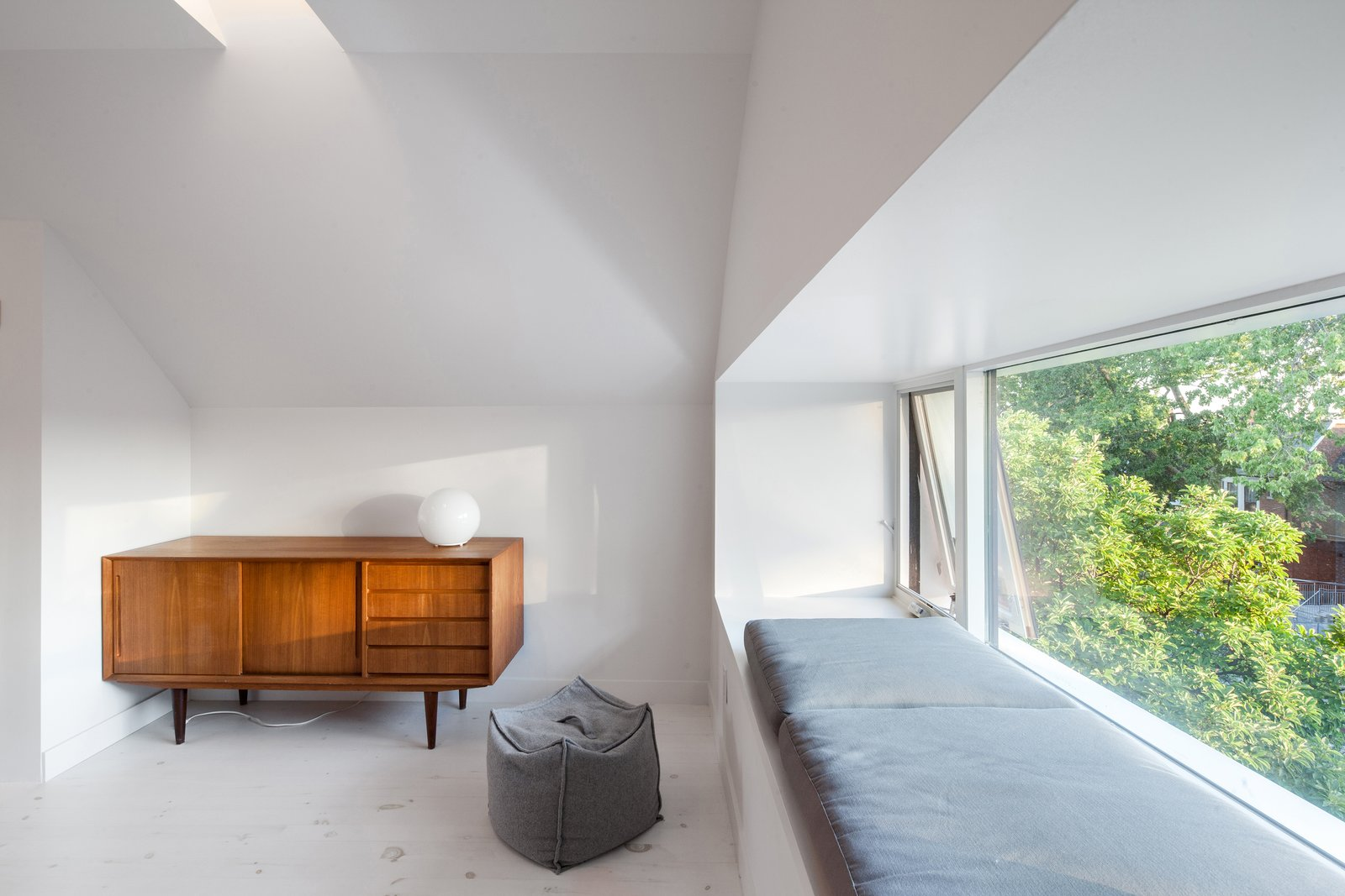 Living Room, Console Tables, Ottomans, Light Hardwood Floor, Bench, and Table Lighting Window  nook overlooking neighbourhood trees and street  House Grace by uoai studio
