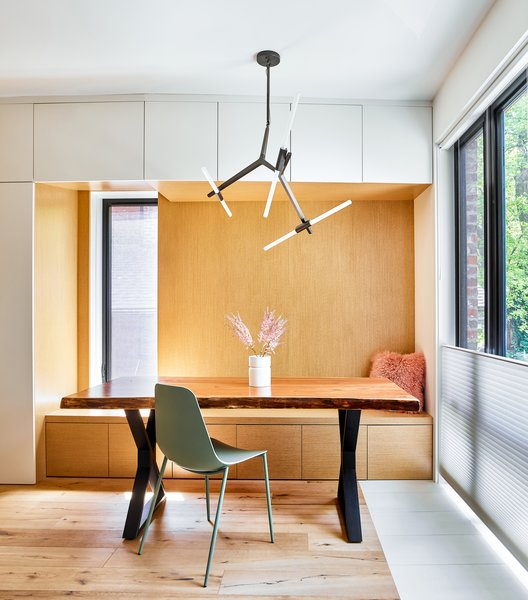 Dining area is defined by wood lined recess.