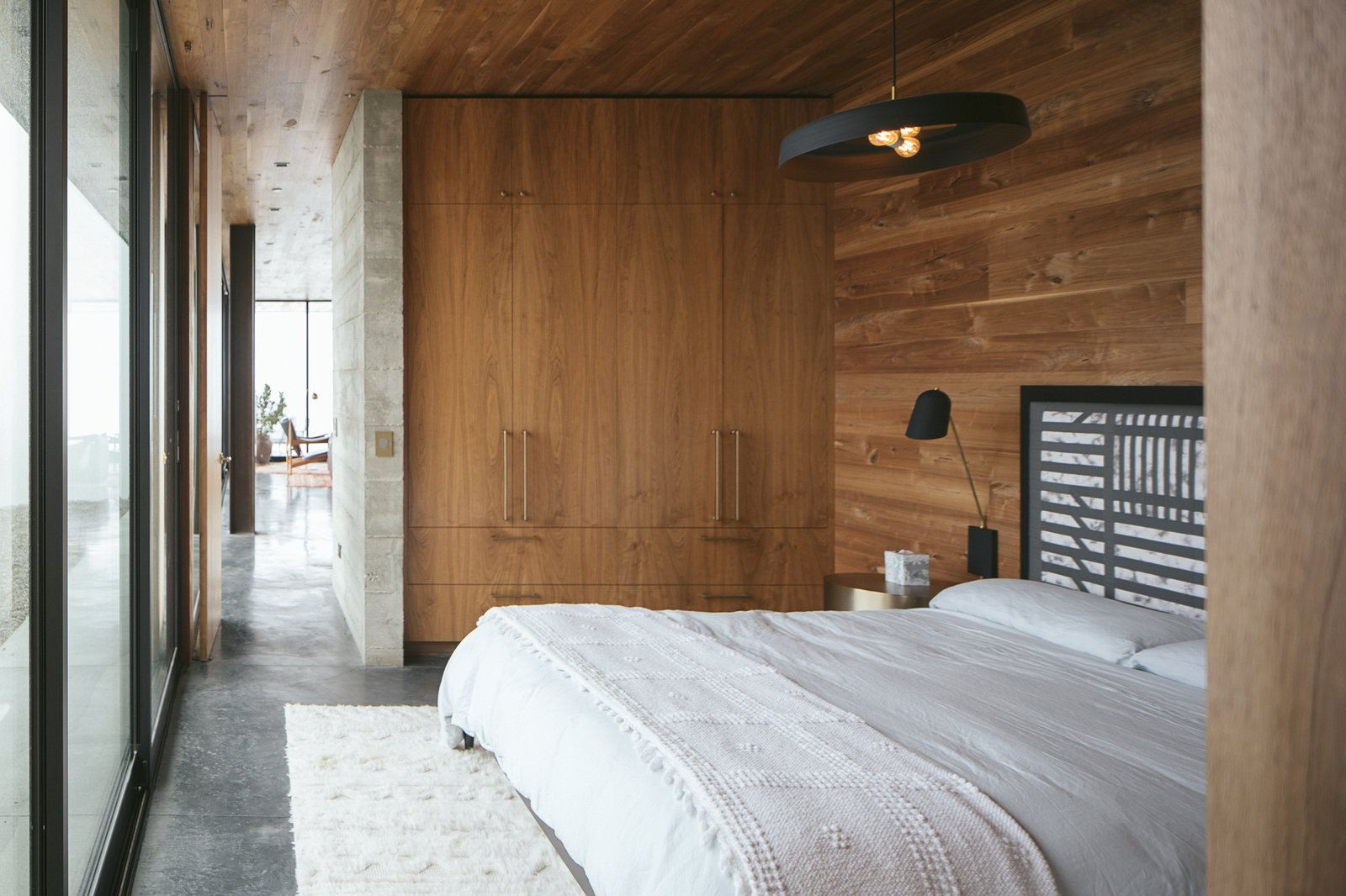 Bedroom with wood wall finish and large black hanging ceiling pendant light