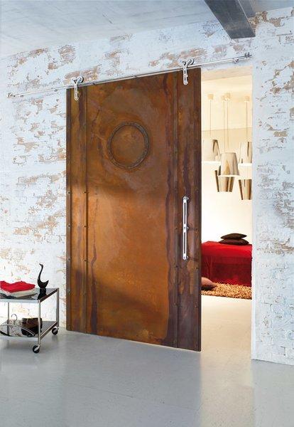 Wood barn door utilizing a modern barn door hardware as an entrace to a bedroom.