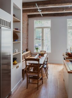 This renovated 19th-century Harlem brownstone is teeming with organic materials and textures, including reclaimed wood beams and boards, stone floors, and Moroccan tile. In the kitchen, antique hand-hewn beams sit overhead, mirrored by reclaimed heart pine flooring. Adding to the charm are exposed brick and a restored antique Biedermeier bench that was custom fit as a banquette.