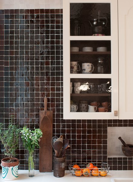 The mixture of dark colored hand-made Moroccan tile backsplash by Mosaic House is offset by  contrasting niche lined with light-colored tile. The custom kitchen cabinets were designed by MIRIAM BIOLEK Interior Design with Bendheim's mouth-blown glass inserts.