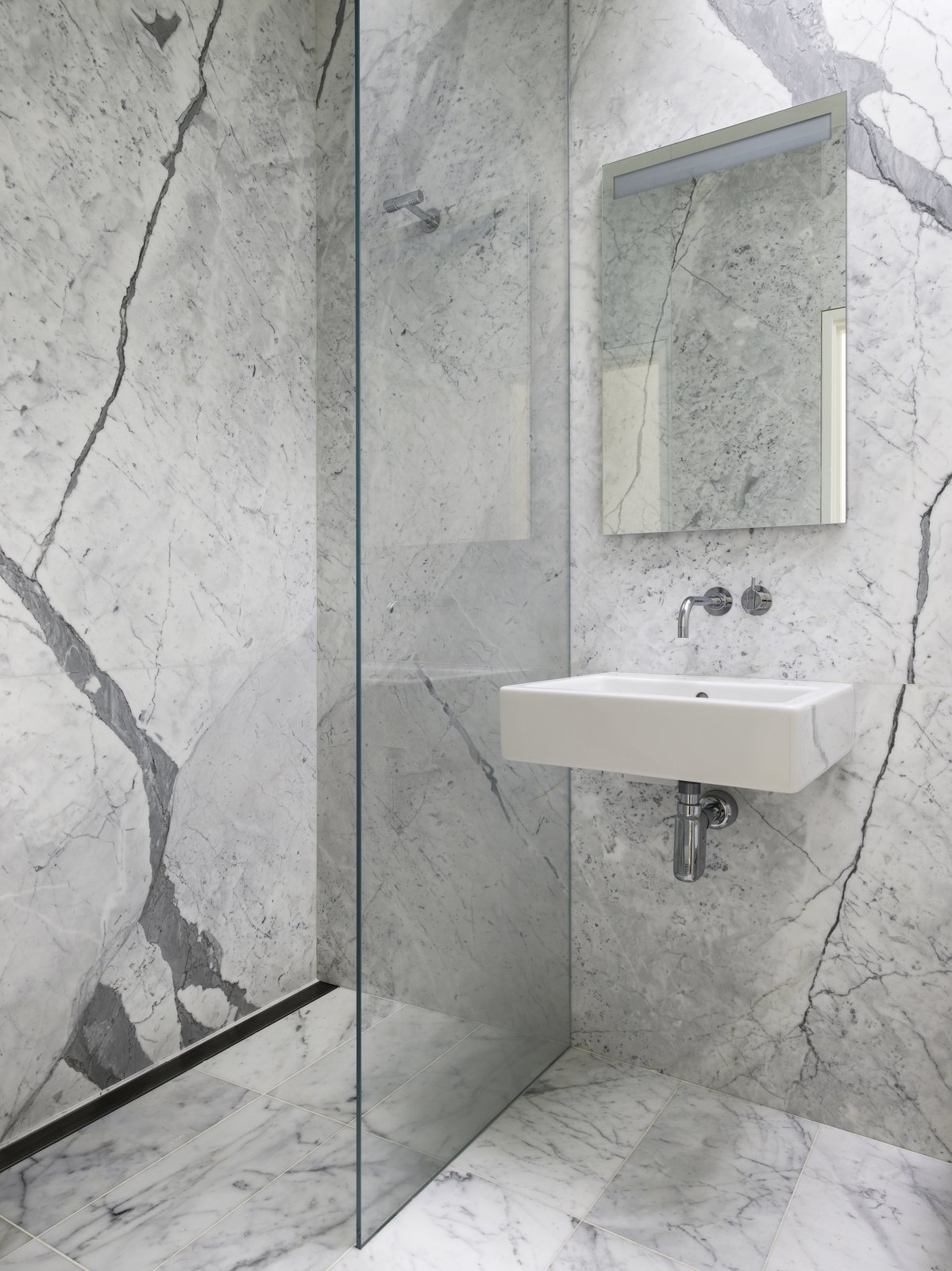 View of the Powder Room, which also doubles as the Guest Bathroom. The same stone as used in the Kitchen is used the Bathrooms for continuity. The wall hung lavatory is by Duravit, the medicine cabinet with integral lighting is by Sidler and all fixtures are by Vola.  Telegraph Hill Periscope by Samaha+Hart Architecture