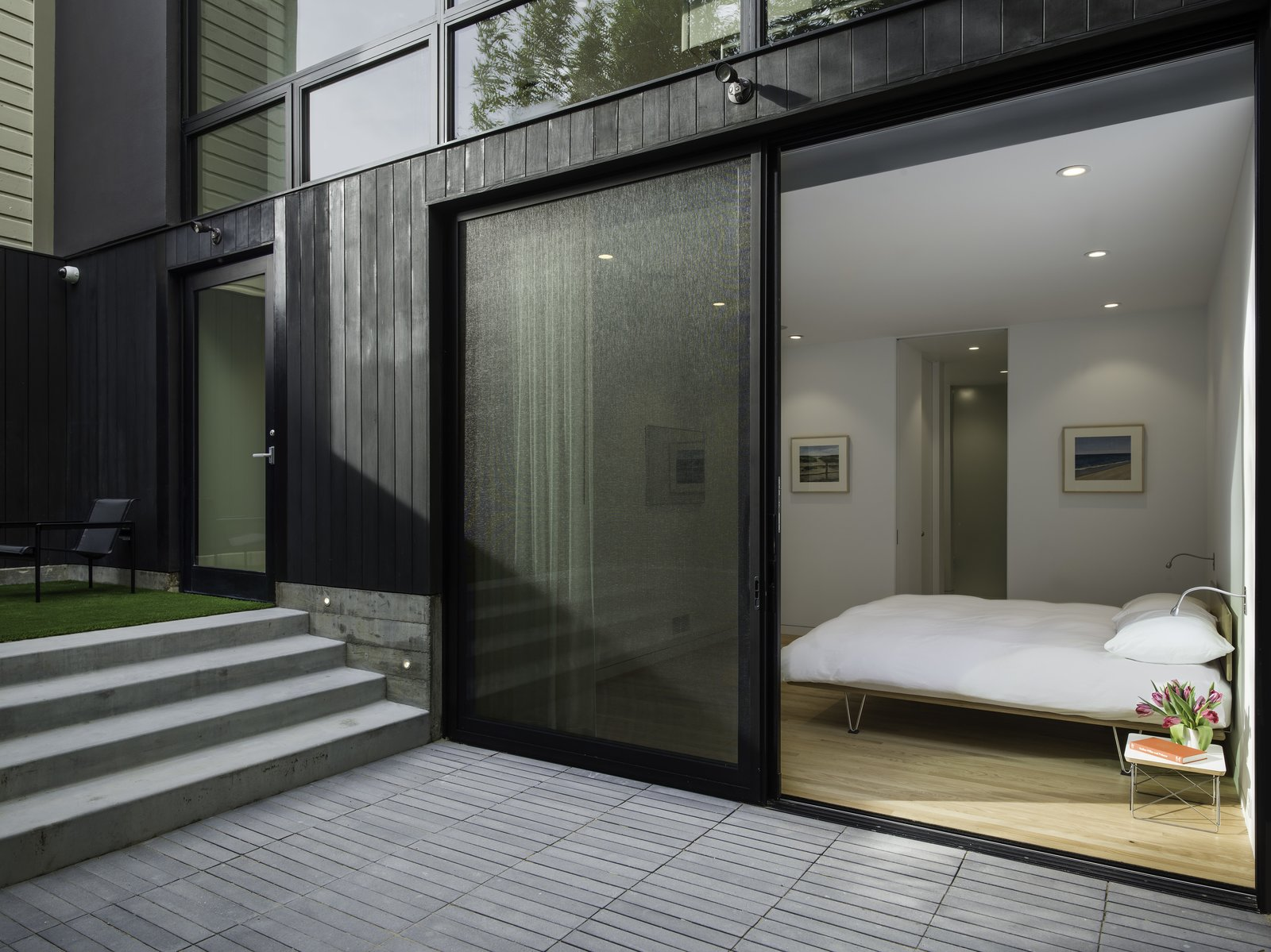 View of the Master Bedroom from the Sunken Courtyard. The same colored concrete pavers are used at the Sunken Courtyard as the Roof Deck-Sun Room for continuity.  Telegraph Hill Periscope by Samaha+Hart Architecture