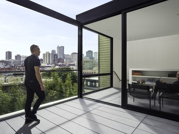 View of the San Francisco skyline from the Roof Deck and Sun Room. The same colored concrete pavers are used in both spaces to blur the relationship between the indoors and outdoors. The owners selected the 1966 collection of outdoor furniture by Knoll which contributes to this effect.  Telegraph Hill Periscope by Samaha+Hart Architecture