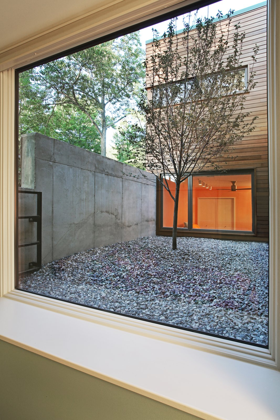 View from basement bedroom into courtyard  Higgins Lake House by Jeff Jordan Architects