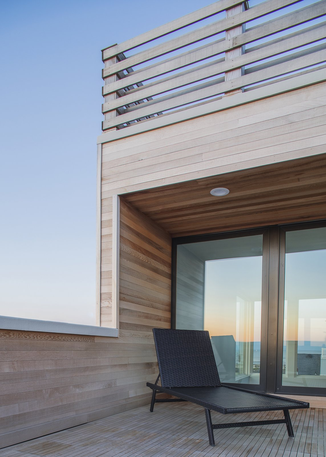 Outdoor, Rooftop, Wood Patio, Porch, Deck, Horizontal Fences, Wall, Decking Patio, Porch, Deck, and Wood Fences, Wall Riverside deck looking through house to ocean at dusk  Sea Bright House by Jeff Jordan Architects