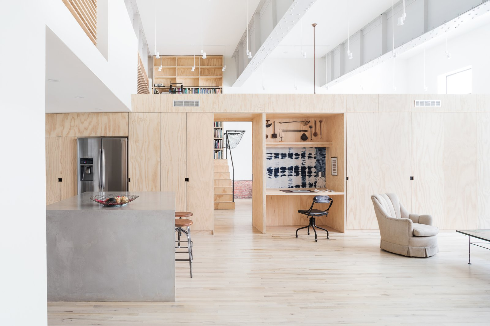 """Living Room, Chair, Coffee Tables, Recessed Lighting, Track Lighting, and Light Hardwood Floor Living space looking toward central organizing """"spine"""" built entirely of plywood  Wells Fargo Loft by Jeff Jordan Architects"""