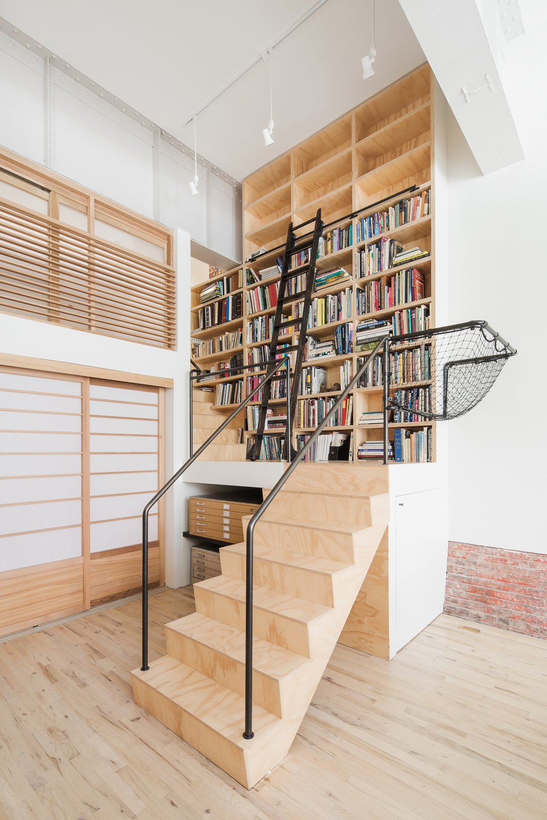 Stair leading to loft bedroom and library Tagged: Office, Library, Craft Room, Study, Storage, Shelves, and Light Hardwood Floor.  Wells Fargo Loft by Jeff Jordan Architects