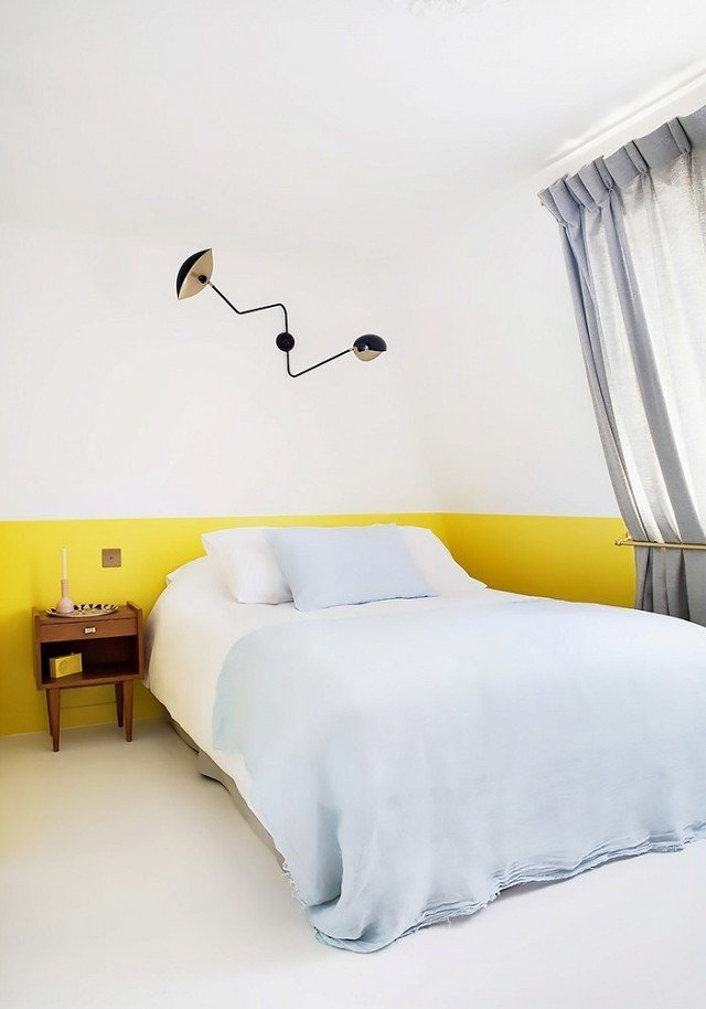 As a paint color, chartreuse can really make a space pop. Playing off soft blue bedding and bright white walls and floor, the yellow hue adds an element of whimsy to a minimal bedroom design.  Photo courtesy of Hotel Henriette  #chartreuse #colorcrush #color #yellow #design #mydomaine  Our Latest Color Crush is Perfect for Summer