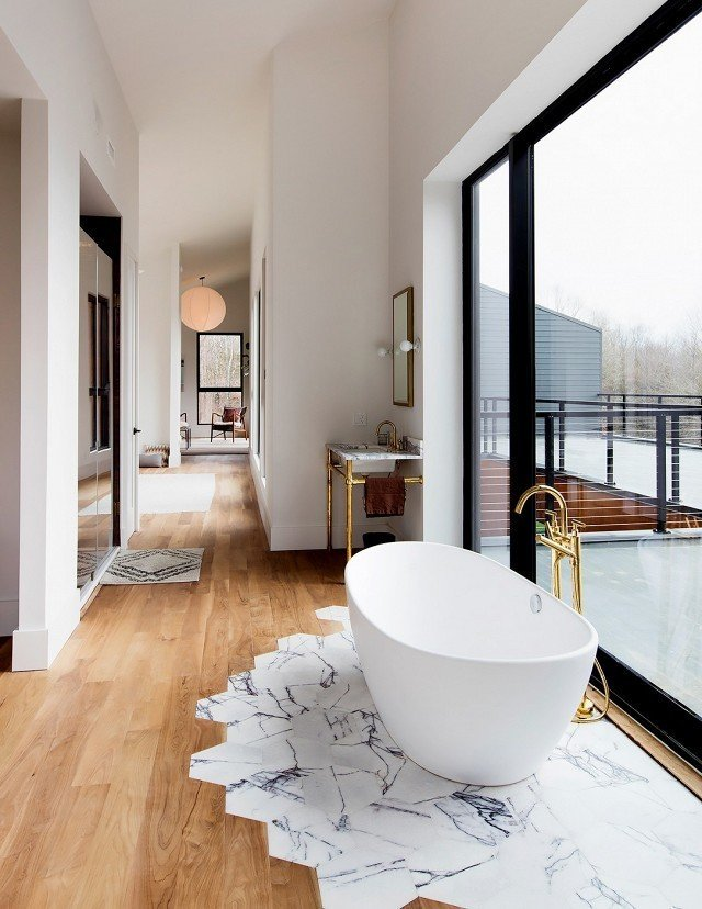 """Bath Room, Freestanding Tub, Pedestal Sink, and Medium Hardwood Floor It might look complicated, but Studio DB's Britt and Damian Zunino, the duo behind this stunning bathroom space, say transitioning tiles to wooden floorboards is surprisingly straightforward. """"The first step is getting your contractor on board, but the actual work isn't that complicated,"""" they told MyDomaine.   Photo courtesy Preston Schlebusch for The New York Times #design #interior #home #tiletransitioning #mydomaine #bathroom  Photo 3 of 9 in How to Use Modern Home Decor in Unexpected Ways from This Gorgeous Home Décor Trend Will Dominate Pinterest"""