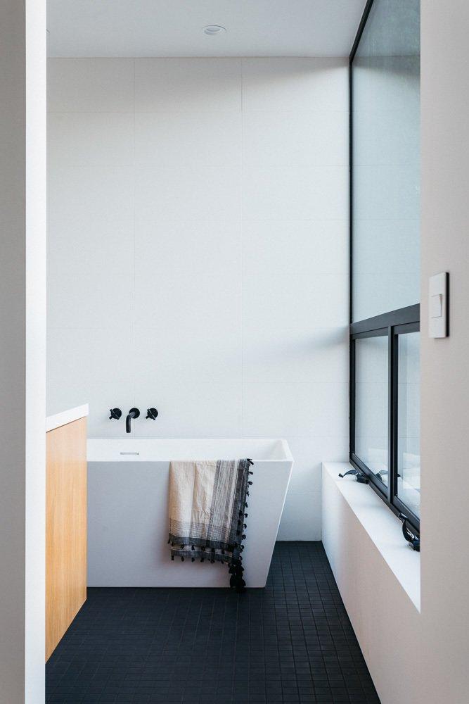 Bath Room, Porcelain Tile Floor, Engineered Quartz Counter, and Freestanding Tub Master Bathroom  Tilt-Shift House by ANX / Aaron Neubert Architects
