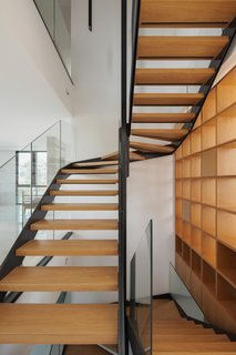 The sweeping staircase in CK House by Christiana Karagiorgi Architects runs alongside the home's wooden library.