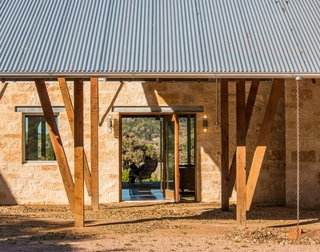 The porte cochère is the main entry to the house. A mahogany-and-glass pivot door allows you to see through the Great Room to the back porch and the valley beyond.