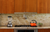 """The kitchen was designed to be as sleek and minimalist as possible, yet remain """"warm"""" to the eye. Unlike a range, a cooktop and oven do not disrupt the line of the countertop.  The range hood is mostly hidden and only shows a thin horizontal line tucked within the line of the cabinets. It pulls out when in use, and slips back into line with the cabinets when not. Photo 8 of The Goat Sheds modern home"""