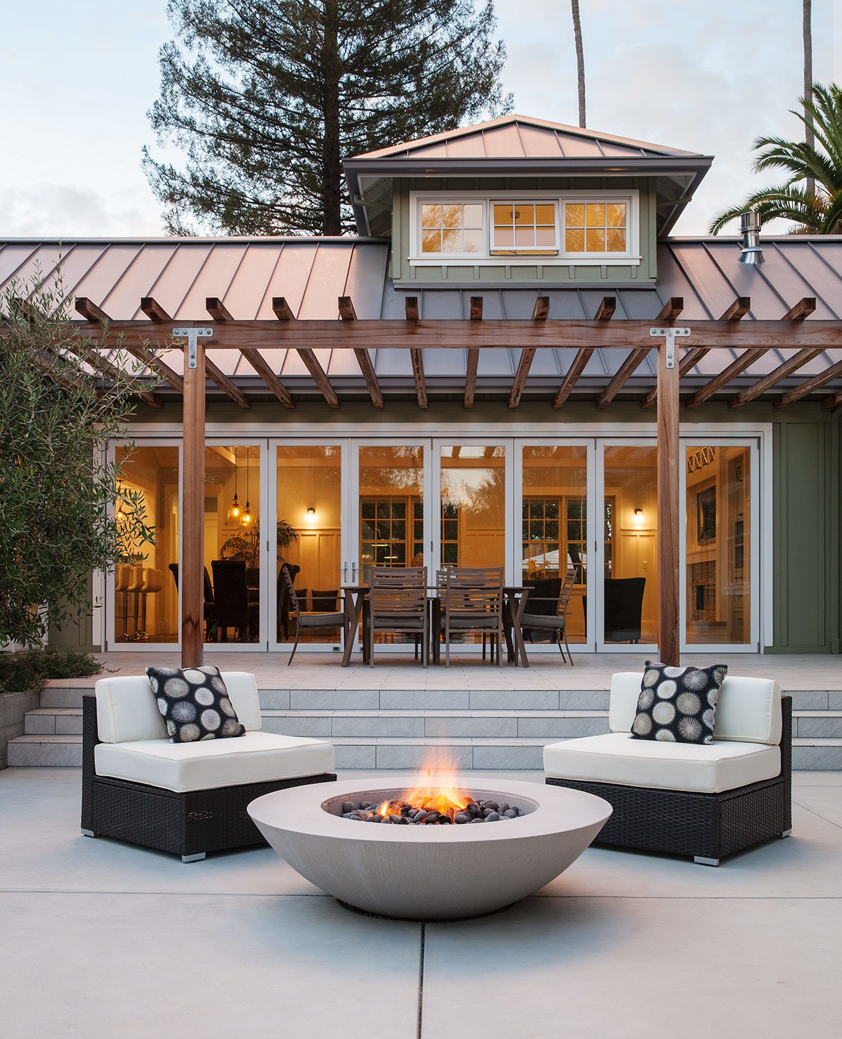 The generous outdoor living area has room for dining and relaxation.  By Arterra Landscape Architects  Talk of the Neighborhood by Arterra Landscape Architects