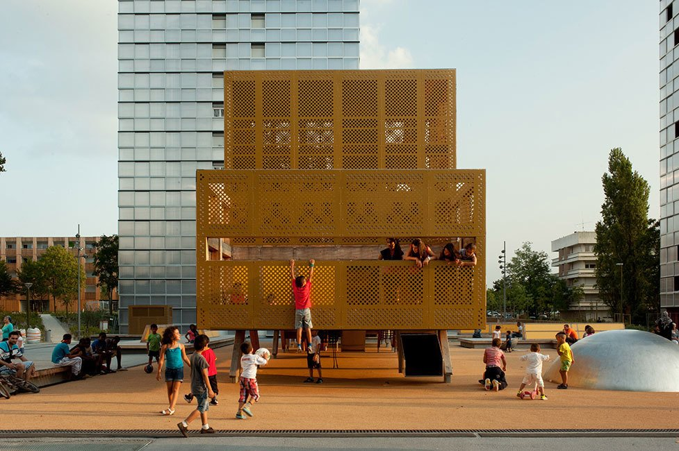 A team of thirty designers and architects developed this perforated playful structure in Bordeaux, France. This chic industriel playground is a modern addition of the Génicart housing community of the 1960s. It revives the spaces with complementary rectangular lines, a sunlit hue, and a compact hub for children to gather and play.  Photo 3 of 11 in 10 Playgrounds With Modern Twists
