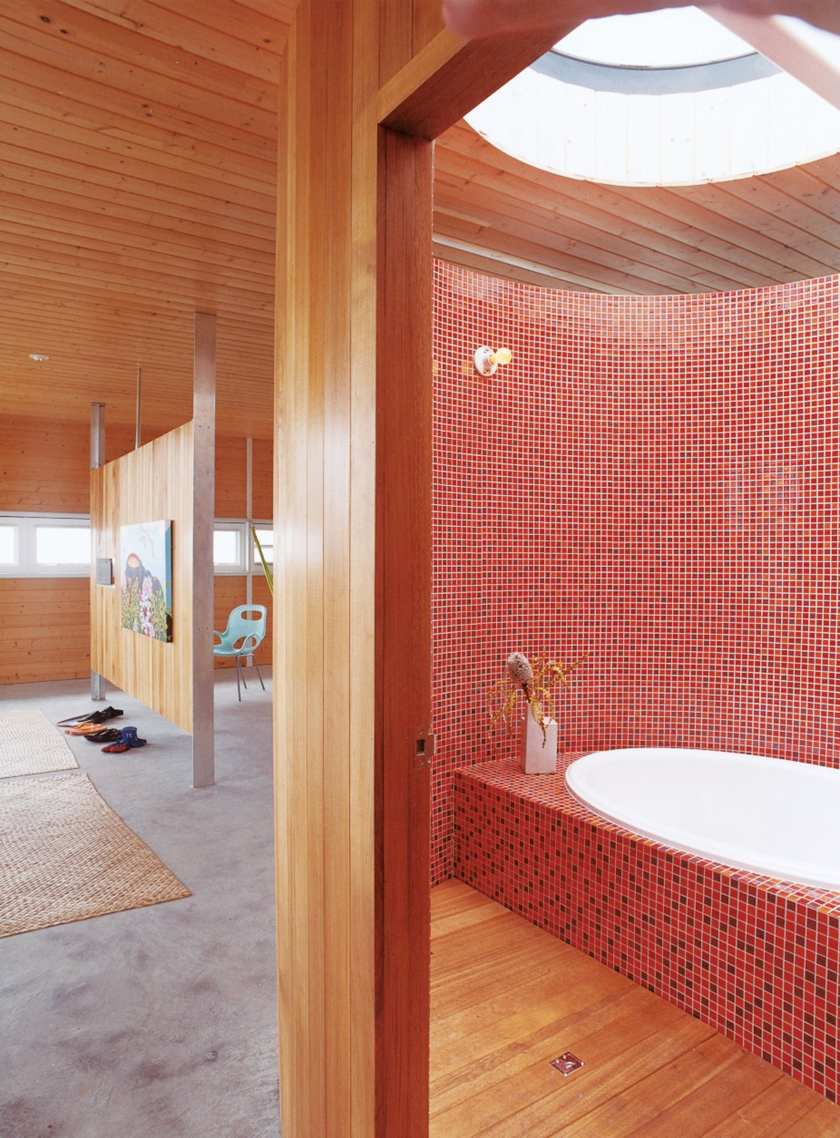 Bath Room, Drop In Tub, Ceramic Tile Wall, and Medium Hardwood Floor Fiery mosaics tile the majority of this Hawaiian tub room. Built and occupied by architect Craig Steely and his wife, the rest of the home is just as warm and tranquil aptly named Lavaflow 2.  Photo 20 of 20 in 20 Bathrooms With Transformative Tiles