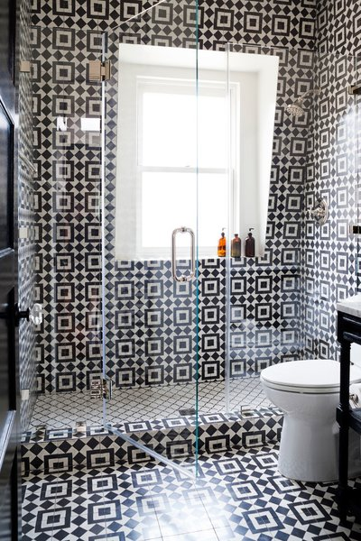 Monochrome tiles define the shape of this transparent bathroom shower. Designer Stacy Zarin Goldberg of Breeze Giannasio Interiors filled this space with thick visual texture and functional designation between the shower floor and the rest of the room.