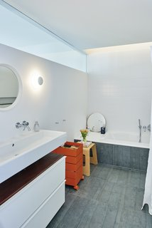 A horizontal glass pane stretches the length of the bathroom, illuminating the redesigned space from above.