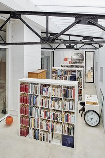 """To house the family's extensive book collection, the team replaced a leaky fiberglass roof above an existing """"winter garden"""" with an insulated glazing system. """"This allowed year-round library use and improved daylighting,"""" adds the firm."""