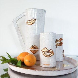 """Beverage Serving Set  $600.00 Got guests? Show them some love with an iced cold beverage served up with a golden kiss! The LUX / EROS Golden Kiss beverage 4 piece set comes with:  10"""" tall Carafe 2 -  5"""" tall Tumblers 12"""" di Hand painted Serving Platter  All LUX / EROS products are handmade, hand carved and hand glazed to order... so every piece is unique! Because of the handmade nature of golden goodies please allow 4-6 for delivery as well as for variances in size and quality.   MADE WITH LOVE, Desanka of LUX / EROS  - Made to order with a 4-6 week delivery.  - Hand rinse only."""