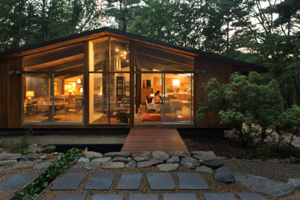 The exterior terrace, water channel, deck, and window wall of Matt and Jon Andersen-Miller's renovated midcentury home.