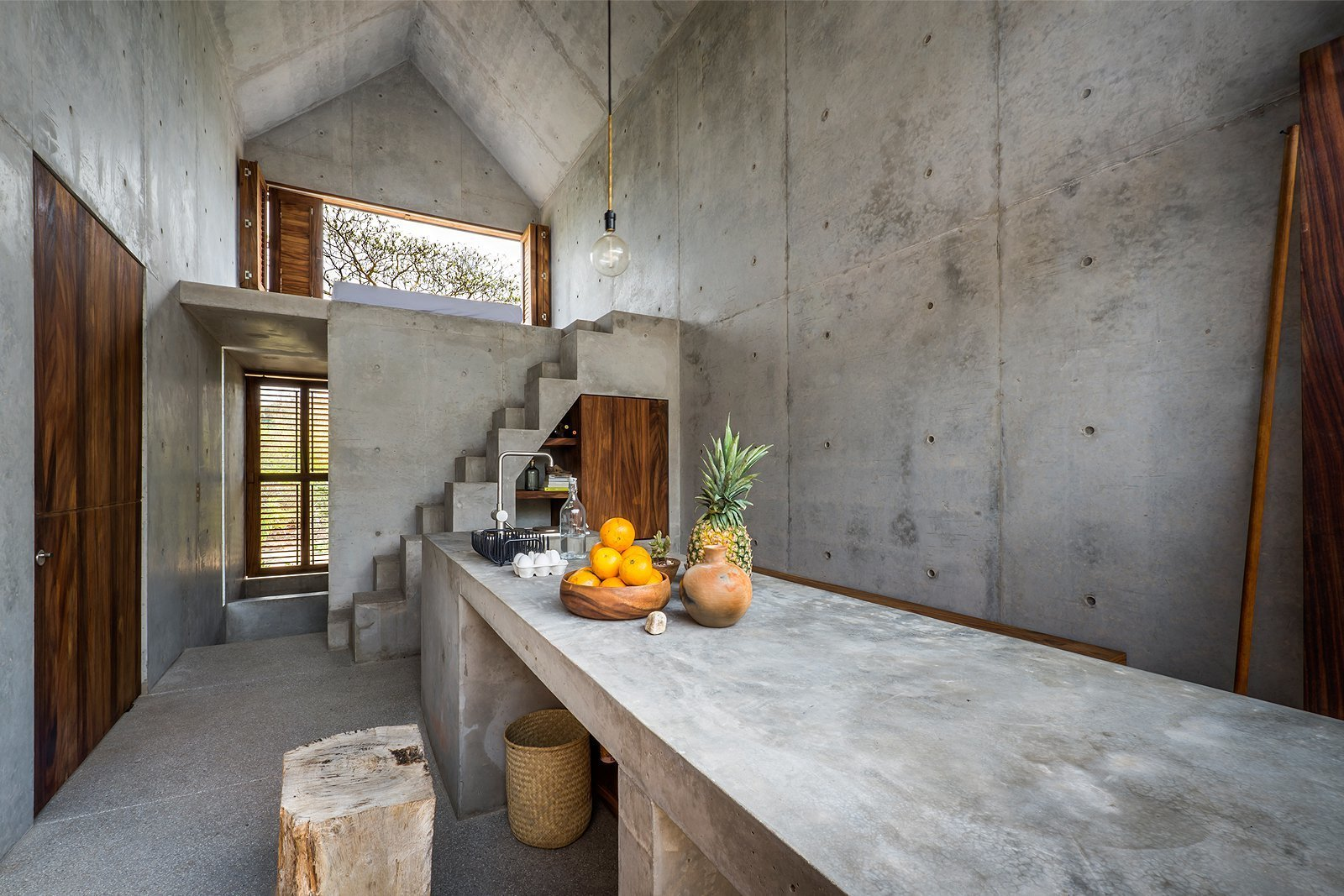 Kitchen, Concrete Counter, Pendant Lighting, Concrete Floor, and Drop In Sink The concrete countertops, walls, and staircase echo the home's refined modern design aesthetic.  Photos from La Casa Pequena