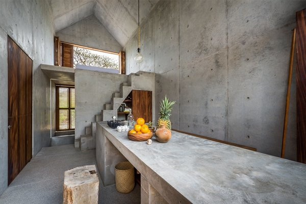 The concrete countertops, walls, and staircase echo the home's refined modern design aesthetic.