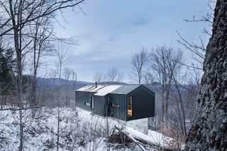 Bolton Residence. Quebec, Canada Architect: _naturehumaine This cantilevered home floats among the trees on a rugged plot of wooded land in Quebec's Eastern Townships. Clad in a black steel skin, the scenery becomes a silent black and white picture in winter.