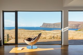 The living room of Wood H by Dualchas Architects has a sweeping view of the surrounding landscape and the Atlantic Ocean.