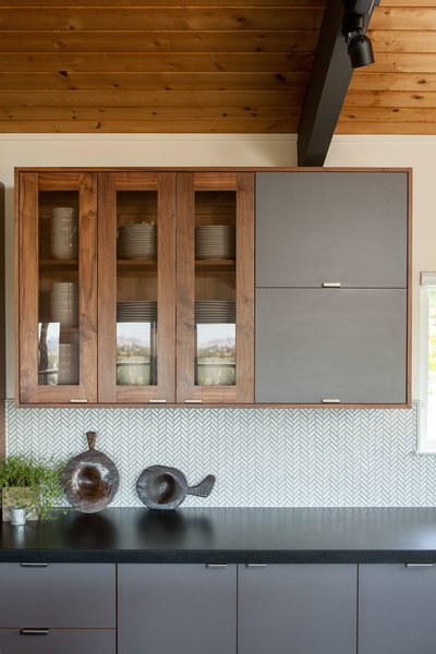 A backsplash laid out in a herringbone pattern adds a subtle layer of texture while pendant lighting adds depth.