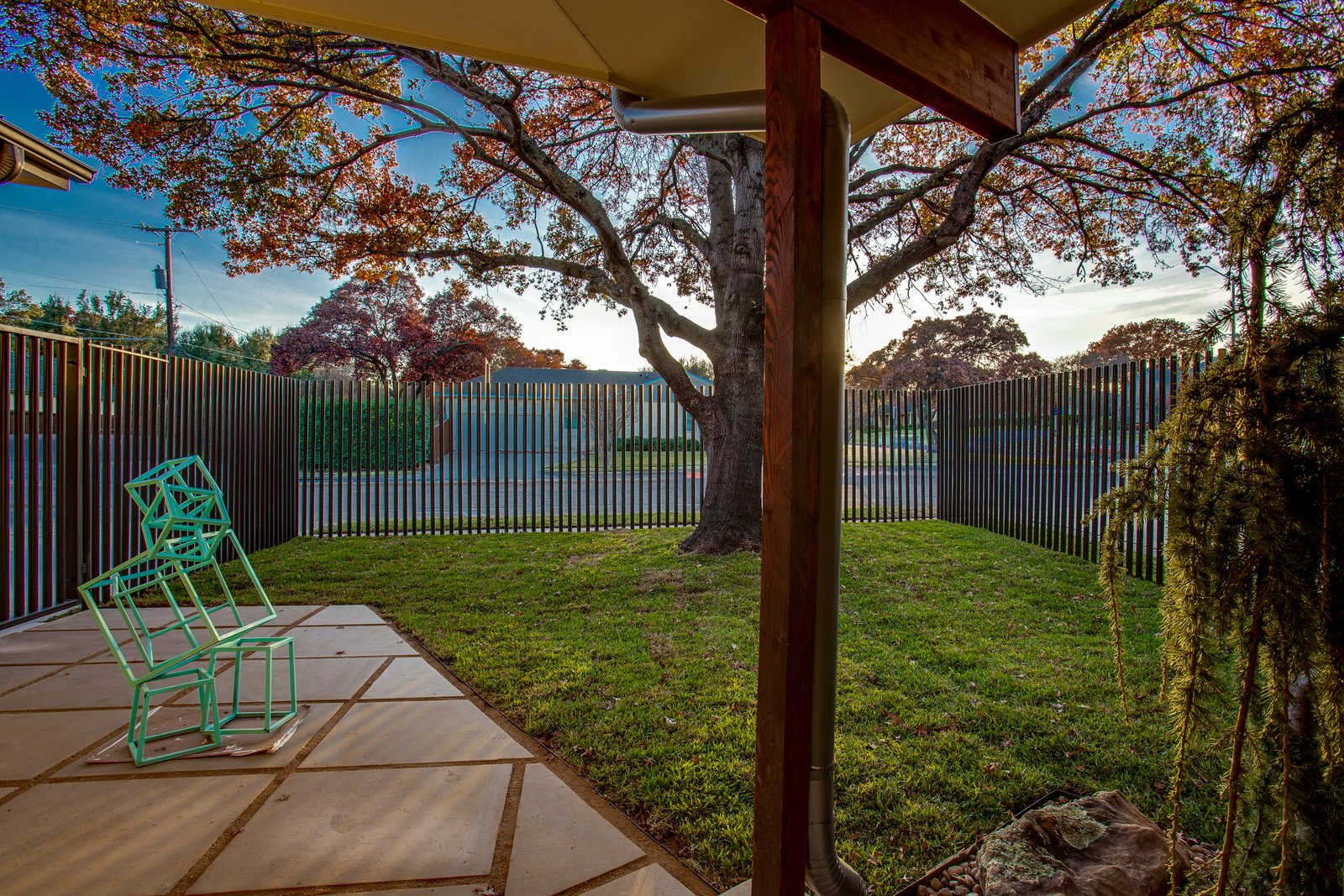 Outdoor, Side Yard, Trees, Hardscapes, Grass, Decomposed Granite Patio, Porch, Deck, Small Patio, Porch, Deck, Vertical Fences, Wall, Metal Fences, Wall, and Stone Fences, Wall South courtyard after  1963 Post and Beam Mid Century Modern by Tavis Westbrook