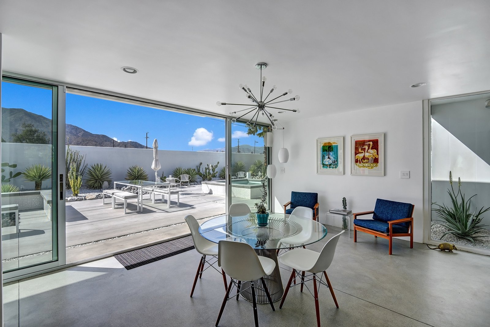 Dining, Lamps, Chair, Ceiling, Floor, Table, and Concrete The 2014 remodel increased light into the home by opening the floor plan.  Best Dining Lamps Table Chair Floor Photos from Donald Wexler Himself Helped Renovate This Palm Springs Prefab Rental