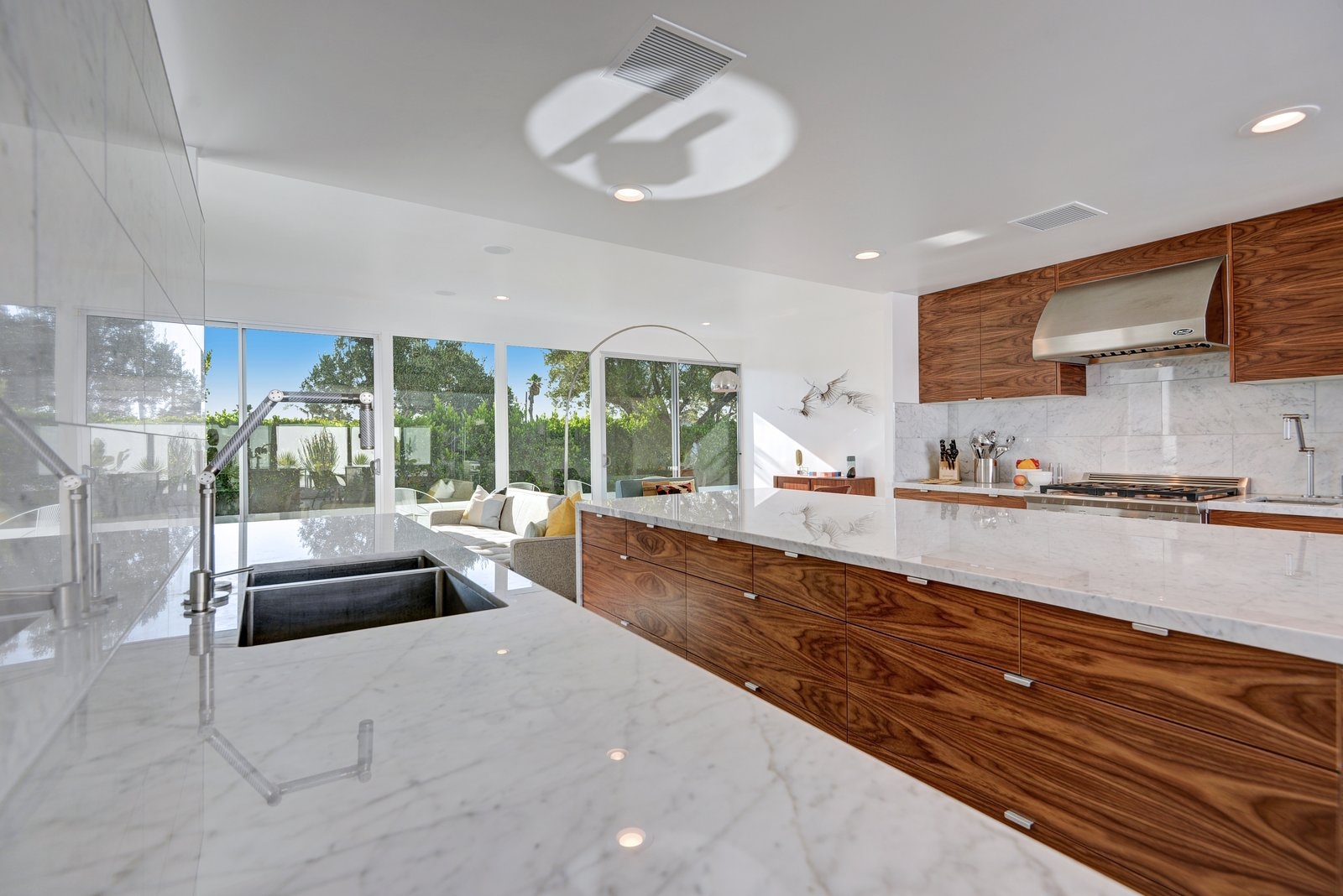 Kitchen, Wood, Refrigerator, Marble, Recessed, Drop In, and Stone Tile To keep the home as open as possible, elements like refrigerator drawers were selected in lieu of traditional appliances.  Kitchen Wood Stone Tile Photos from Donald Wexler Himself Helped Renovate This Palm Springs Prefab Rental
