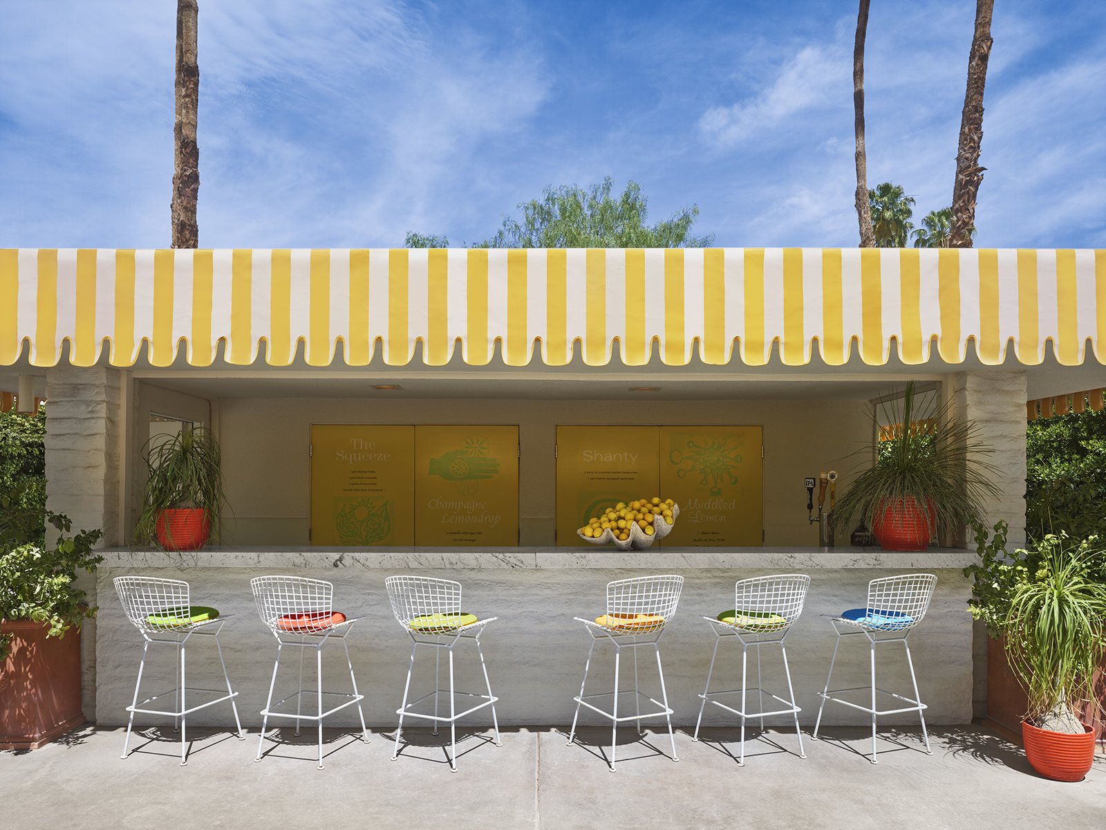 Outdoor, Desert, Trees, Concrete Patio, Porch, Deck, and Planters Patio, Porch, Deck The lemonade stand at the Parker Palm Springs, complete with Bertoia Barstools  Photo 3 of 7 in Jonathan Adler Reveals His Redesign of the Parker Palm Springs