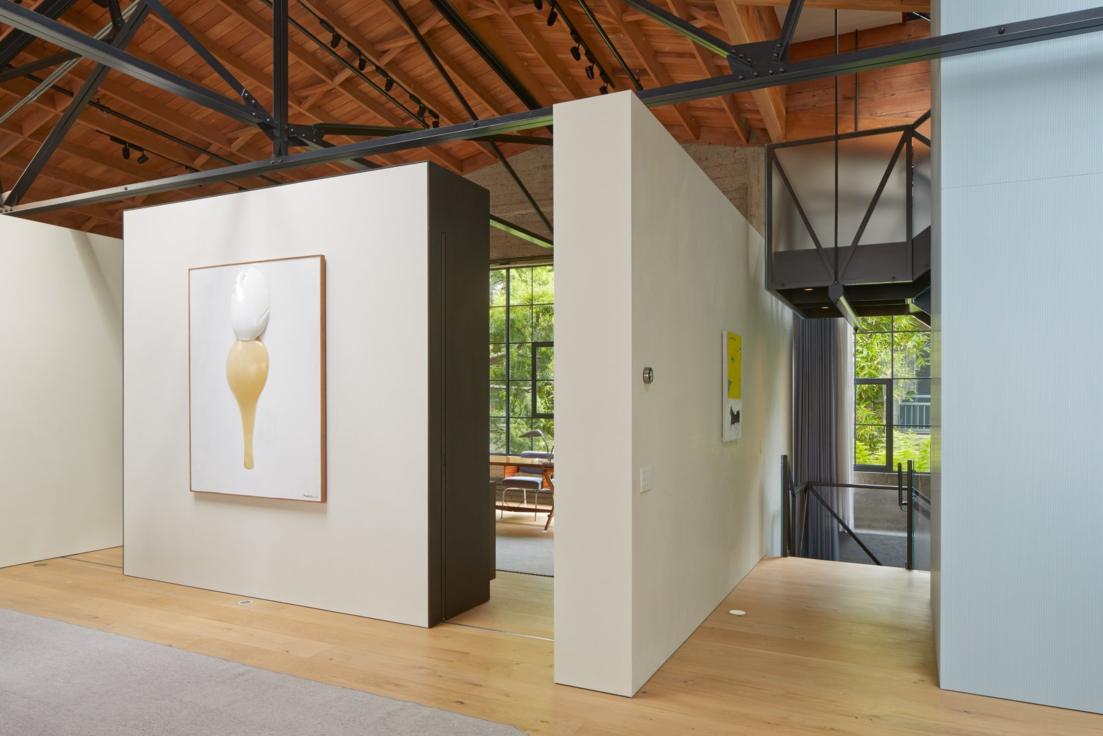 """Hallway and Light Hardwood Floor Free-standing walls highlight the couple's noteworthy art collection. """"The owner has a phenomenal eye,"""" says architect Martin Marciano. """"She could be curating in any modern art museum.""""  Photo 1 of 13 in A Knitting Mill in San Francisco Becomes an Unbelievable Loft For Two Art Collectors"""