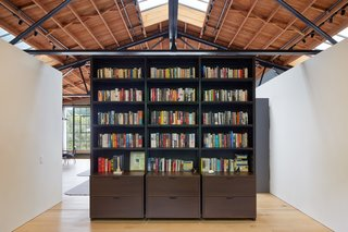 """Fiedler Marciano Architecture crafted not only the loft, but also many of the industrial design objects. The bookcase here is part of the """"black"""" family of objects, including the closet storage and stair. The """"white"""" family of object include the bathroom, kitchen, and more."""