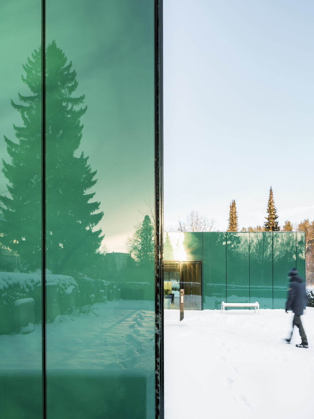 Exterior, Flat RoofLine, Metal Roof Material, Metal Siding Material, and Glass Siding Material One of architect Gert Wingårdhs' favorite parts of the building is the reflective glass.  Photo 2 of 7 in Architect Gert Wingårdh Builds a Dazzling Emerald Office in a Swedish Cemetery