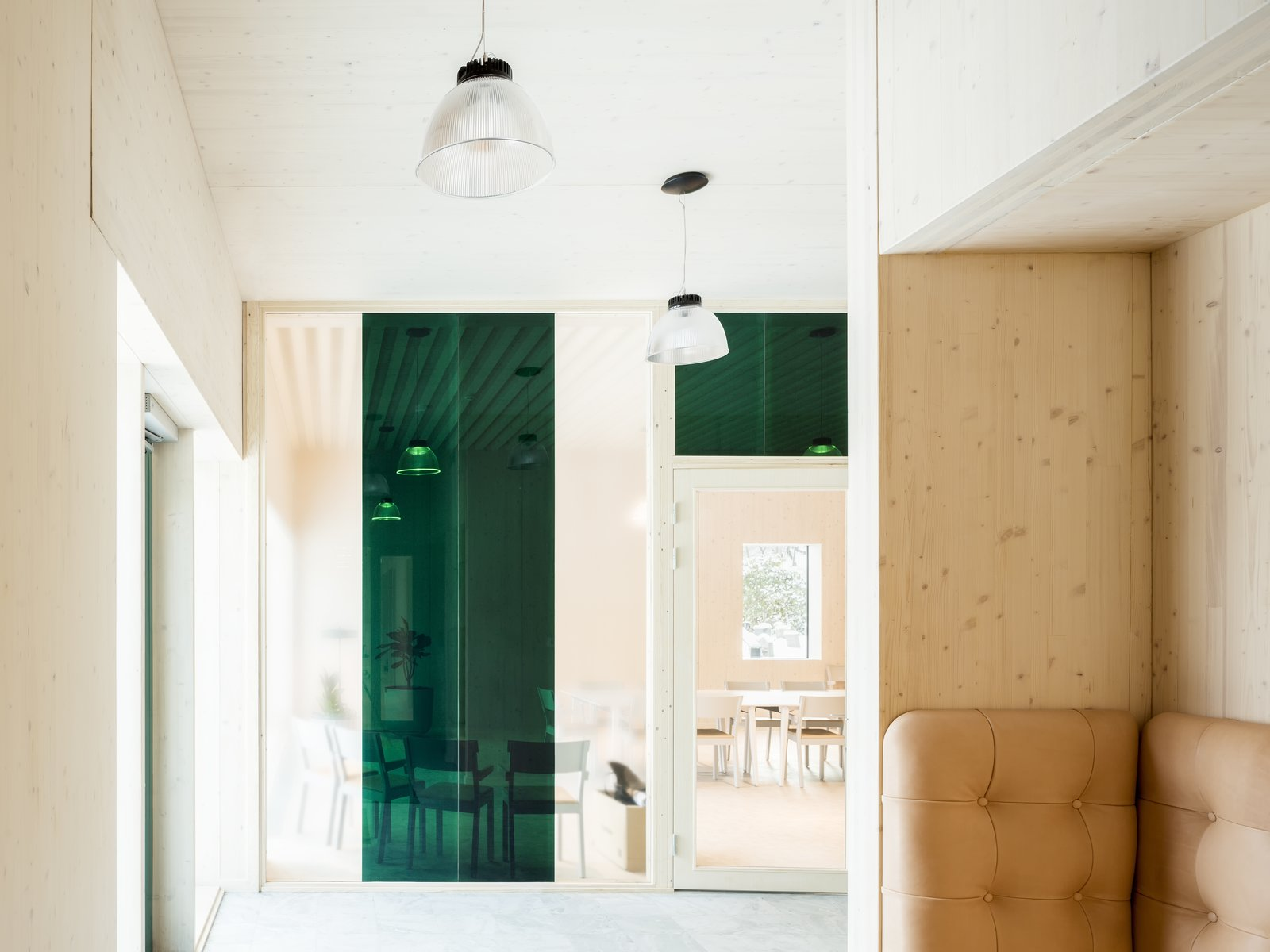 Office and Concrete Floor The interior design is characterized by restraint. Wood complements leather and concrete for a modern, natural-looking building that blend together with its lush surroundings.  Best Photos from Architect Gert Wingårdh Builds a Dazzling Emerald Office in a Swedish Cemetery