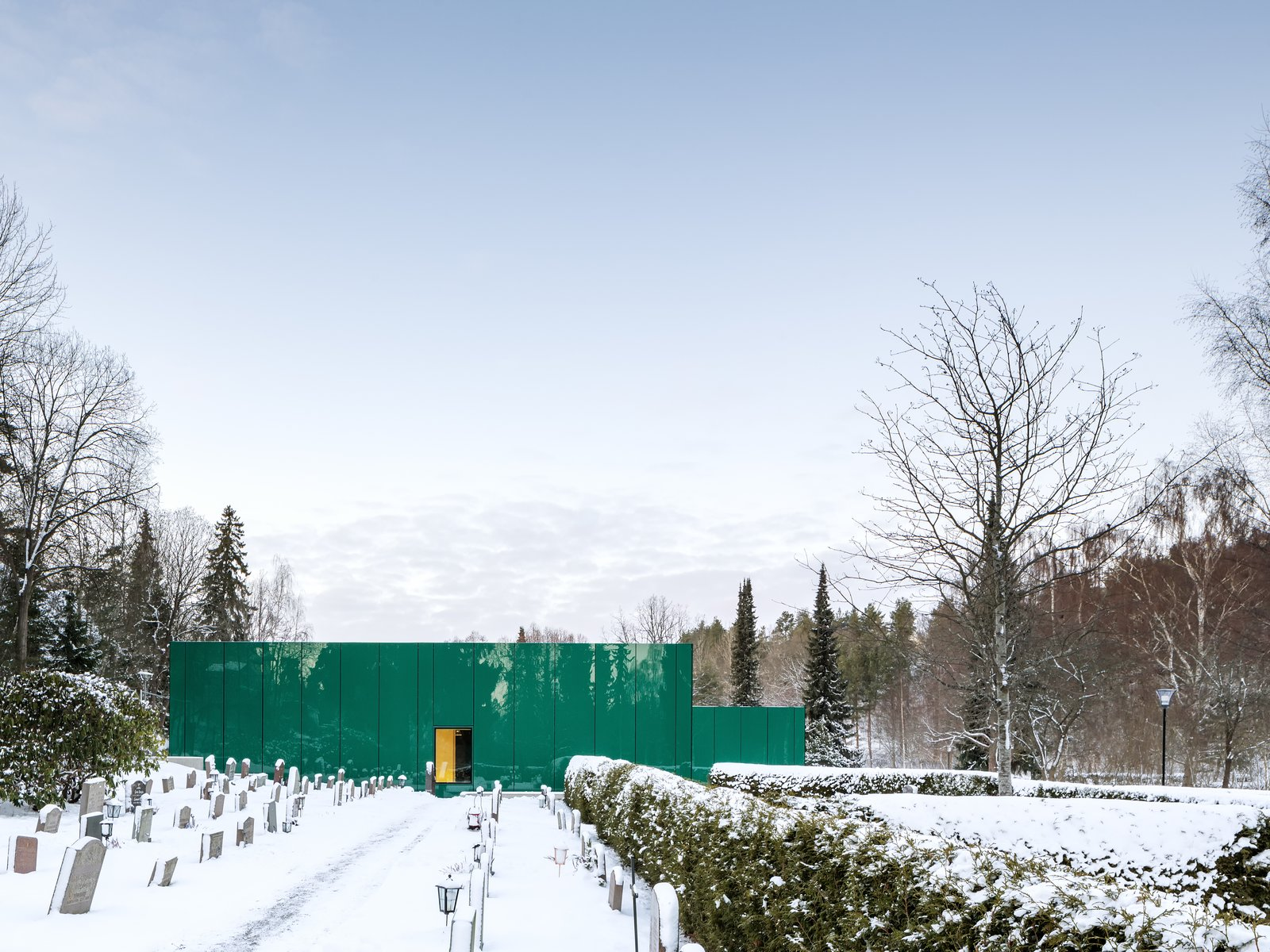Exterior, Metal Roof Material, Flat RoofLine, Metal Siding Material, and Glass Siding Material The green glass reflects the surrounding vegetation, integrating the building into the garden spaces framed by the cemetery's hedges.   Photo 6 of 7 in Architect Gert Wingårdh Builds a Dazzling Emerald Office in a Swedish Cemetery