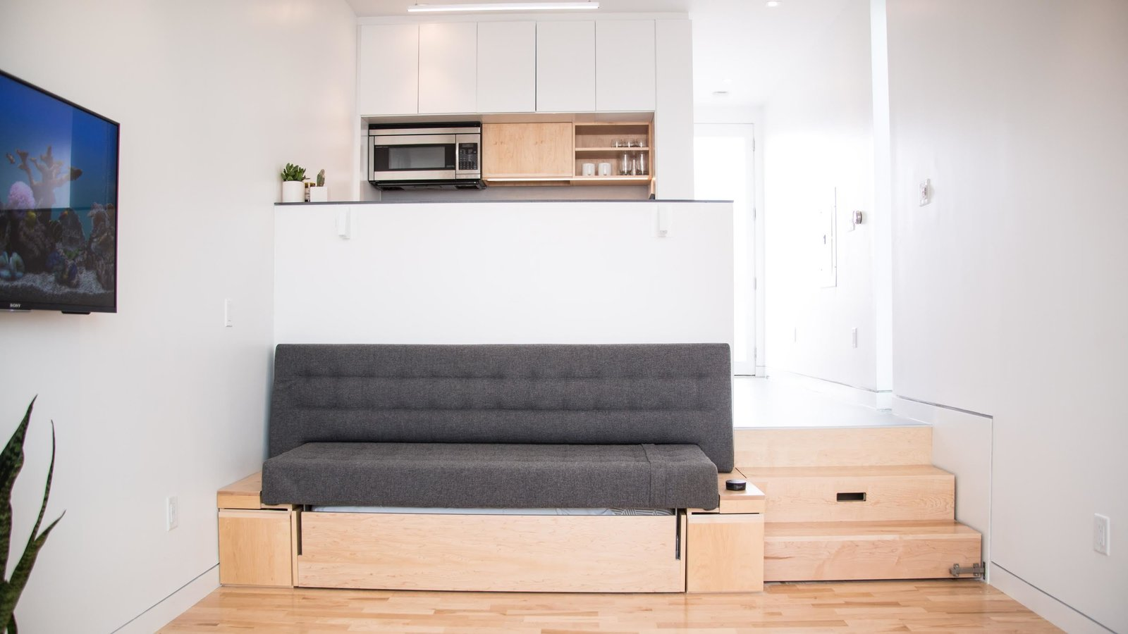 Living Room, Sofa, Light Hardwood Floor, and Storage The sofa converts to a queen-size bed complete with a Casper mattress. Bedding tucks away neatly in the storage below.  Photo 3 of 9 in Can These Tiny, Modular Smart Homes Relieve the Demand For Affordable Housing?