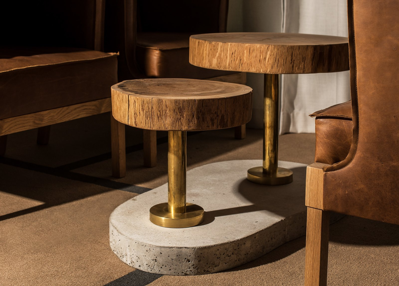 Dining Room, Table, Rug Floor, and Bench Keeping with the principles of organic architecture, few materials were used. Here, leather, brass, oak, and concrete create a natural and warm setting.  Photo 12 of 12 in Run, Don't Walk to This Frank Lloyd Wright-Inspired Bar in Chicago